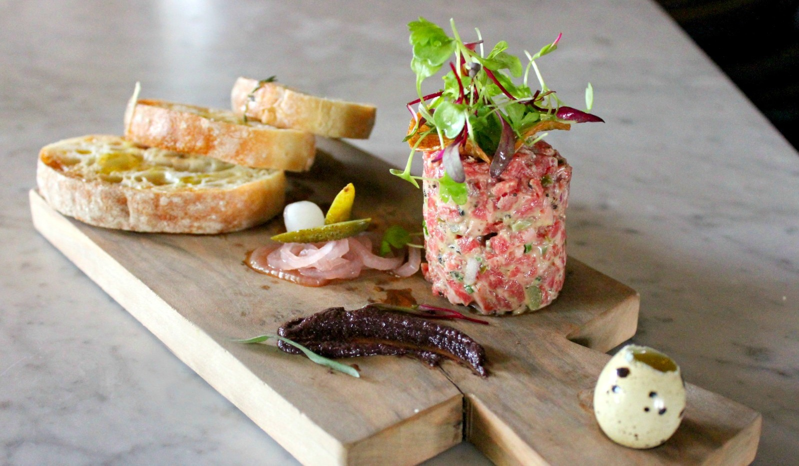 Steak tartare on cutting board with bread slices